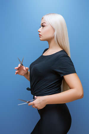 Beautiful blonde woman in black clothes, with scissors in her hands on a blue background, professional hairdresser