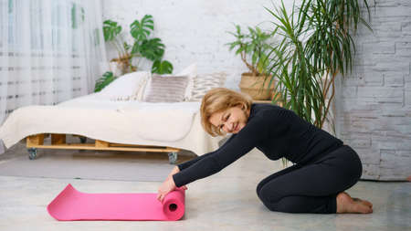 Mature woman reeling off Mat after training at home. Happy time for your health. Bright room with a bed and a window