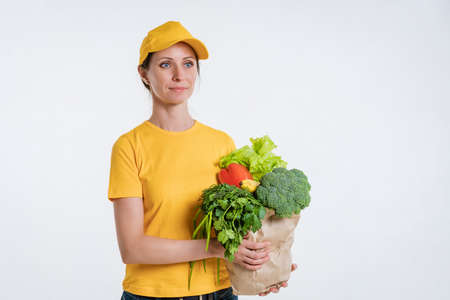 A woman in yellow clothes, delivering a package of food, on a white background Archivio Fotografico