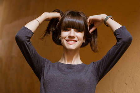 Portrait of a funny young woman holding her hair in her hands and laughing, looking at the camera against an orange wall. A fitness bracelet is on my arm.