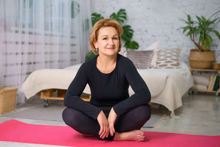 Mature woman in a black tracksuit doing yoga sitting on the Mat at home, against the background of a bed and pots of green plants, healthy lifestyle concept sitting at home