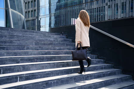 Business woman in a coat with a bag in her hands goes up the steps to the building. The concept of career and business