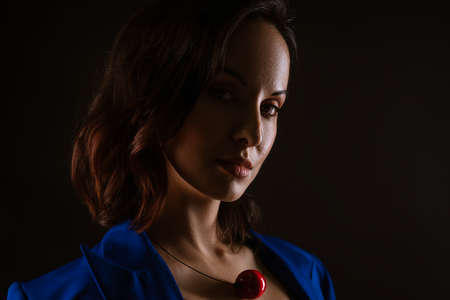 Close-up portrait of a beautiful woman, dark photo on a black background.