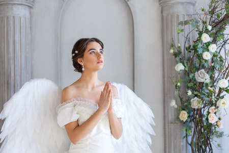 Portrait of a beautiful young woman in a white dress and angel wings, standing with a pleading look against the background of a wall with columns and flowers Stock Photo