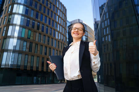 A business woman stands with a laptop in a suit and glasses outside an office building during the day.