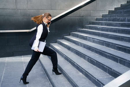 A business woman walks up the steps holding a tablet in her hand and talking on the phone. Conceptual horizontal photo