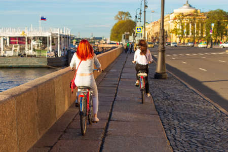 Two happy free women ride a Bicycle in the afternoon along the embankment on a Sunny day, a healthy lifestyle concept