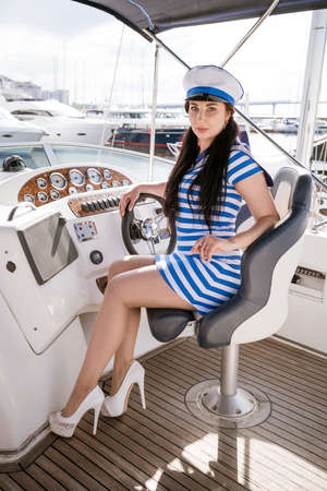 A beautiful young girl captain in striped clothes and in long heels sits in the captain's chair and controls a white ship Imagens