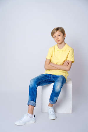 A cute guy in a yellow t shirt and blue jeans on a white background is sitting on a cube and posing