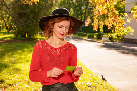 portrait of happy woman in hat hands at the top in autumn Park 版權商用圖片