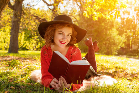 lovely woman reading a book in the autumn Park sitting on the grass 版權商用圖片