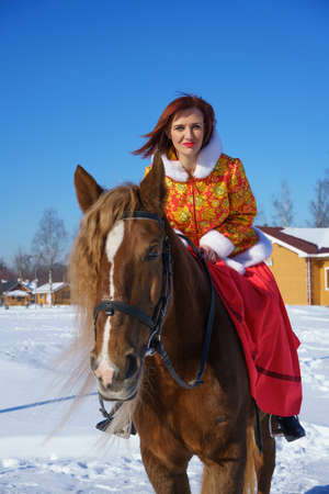 A beautiful young girl in a warm yellow-red jacket rides a horse on a winter sunny frosty day. Is engaged in equestrian sports in the winter season