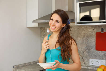 A smiling woman with dark hair and a blue t shirt stands in the kitchen with a spoon in her hand