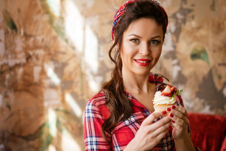 beautiful woman in a shirt with makeup holding a strawberry shortcake, pin-up concept