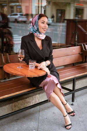 A beautiful brunette woman with bright makeup is sitting in a cafe on the street with a glass of wine Zdjęcie Seryjne