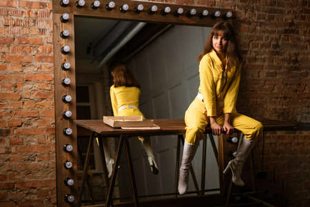 A young cheerful woman in a yellow jumpsuit is sitting on a table with pizza in front of a mirror Stok Fotoğraf
