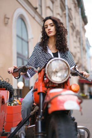 Beautiful young woman brunette with curly hair sitting on a red motorcycle on a city street