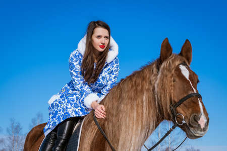 beautiful woman in a blue coat riding a horse in winter on a Sunny day