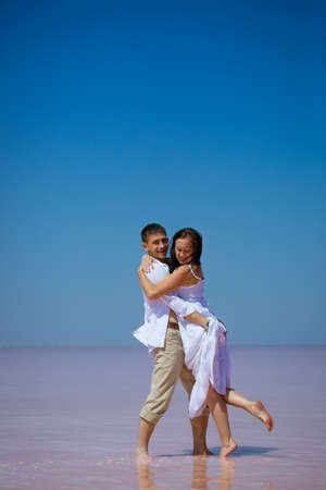 A romantic couple a man and a woman in white clothes dance on a pink lake on a Sunny day,