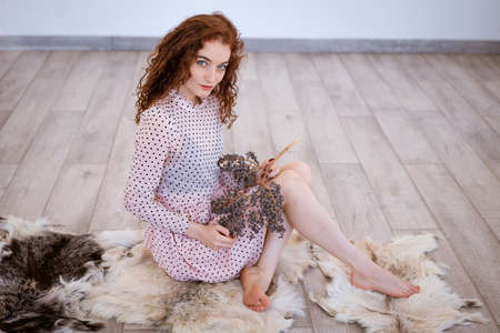 Beautiful red-haired young woman sitting on the floor , the concept of loneliness and depression