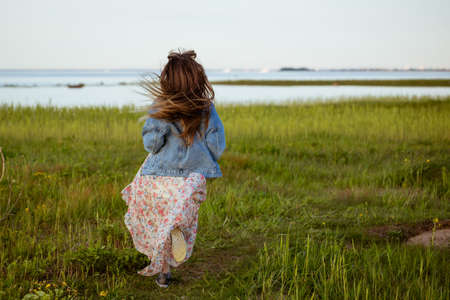 Happy cheerful young woman with long hair running on the grass in nature in a dress Standard-Bild