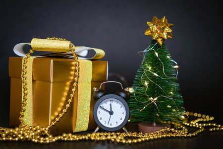 gift box with a gold bow. White alarm clock and a small Christmas tree on a black background.