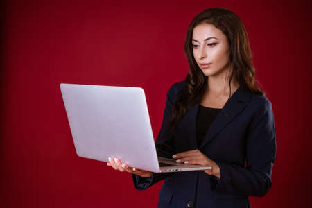 A young woman dressed in a formal suit holds a laptop and decides business matters on a red studio background. Work concept.