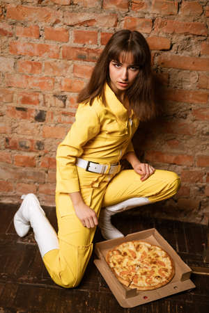 A young woman dressed in a yellow suit is leaning against a brick wall and eating a slice of pizza.
