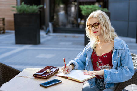 Young woman with glasses, a freelancer sits at a table in a cafe on the street writing in a notebook