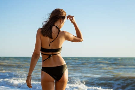 A young brunette woman in a split black swimsuit stands on the seashore. Enjoying the moment. Relaxation.