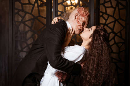an ugly man in a tailcoat kisses a young beautiful brunette in a white peignoir - cosplay for the musical The Phantom of the Opera