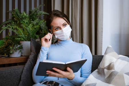 Caucasian woman in a protective mask sits on the couch with a notebook in her hand with a pensive look writes