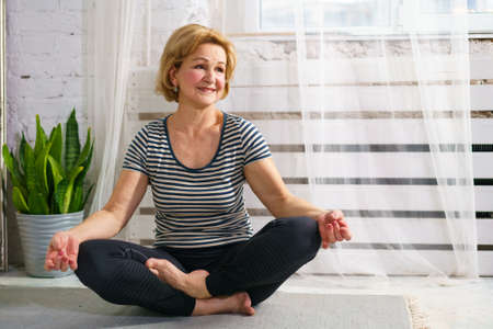 Pretty sporty european mature woman in sportswear meditates at home in the room. Healthy lifestyle in the elderly