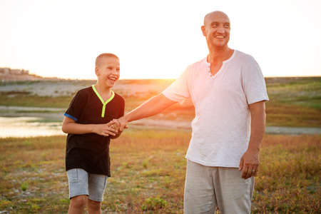 Son and dad standing against the backdrop of a colorful sunset. The relationship between father and son. Familys soulful walk in nature in the rays of the setting sun