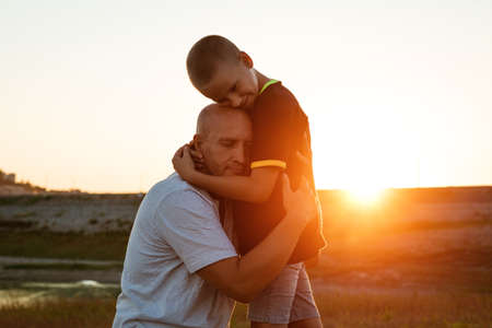 Son and dad standing against the backdrop of a colorful sunset. The relationship between father and son. Familys soulful walk in nature in the rays of the setting sun Standard-Bild