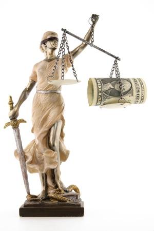 Justice (grec: themis, latin: justitia) les yeux band�s avec des �chelles, l'�p�e et de l'argent sur une �chelle. La corruption et le concept corruption Banque d'images