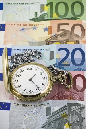 winder: time is money , vintage pocket watch with euro banknotes background Stock Photo