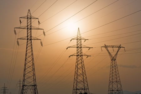 High voltage electricity pylons against sunset