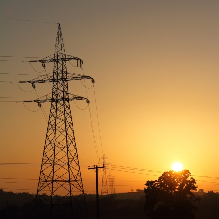 High voltage electricity pylon against sunset photo