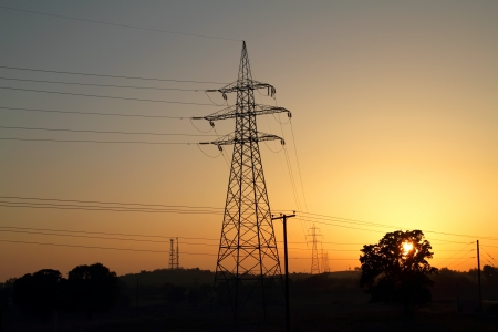 High voltage electricity pylon against sunset
