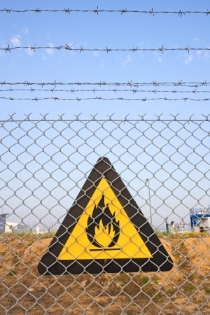 chain link fence: Chainlink and barbed wire fence with fire warning sign