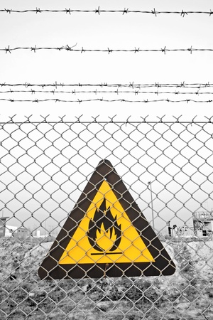 Chainlink and barbed wire fence with fire warning sign Stock Photo - 17721502