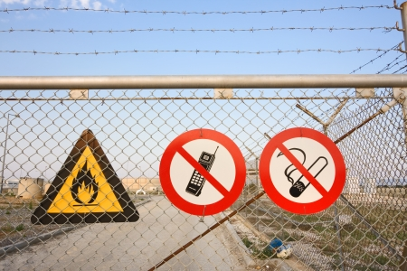 chain link fence: Chainlink and barbed wire fence with warning signs