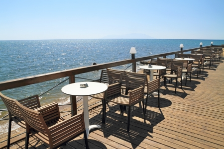 Idyllic cafe restaurant by the sea, on wooden deck photo