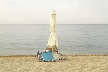 Fin de l'�t� Ferm� parasol et des chaises sur une plage d�serte avec ciel couvert Banque d'images