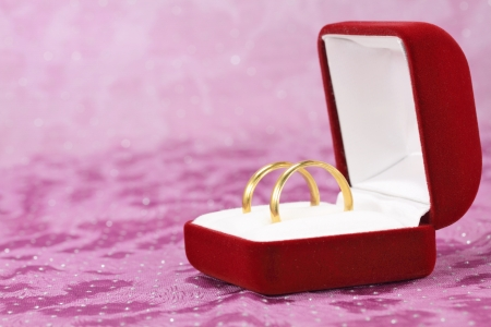 marital: A pair of wedding rings in jewelry box on purple cloth Stock Photo