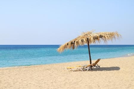 Umbrella and lounge chairs on idyllic beach, in Thassos island - Greece