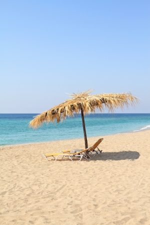 Umbrella and lounge chairs on idyllic beach, in Thassos island - Greece