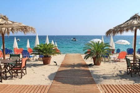 Bar aan het strand met stro parasols en houten dek op exotische oord