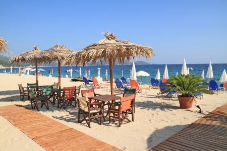 beach bar: Beach bar with straw umbrellas and wooden deck on exotic resort